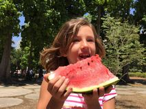 Young girl eating watermelon outdoors Stock Images