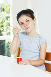Young girl eating a yoghurt Royalty Free Stock Photography