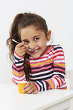 Young girl eating a yoghurt, smiling Stock Image
