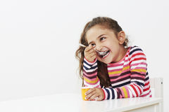 Young girl eating a yoghurt, smiling Royalty Free Stock Photography