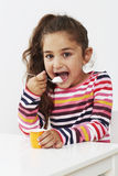 Young girl eating a yoghurt Royalty Free Stock Photos