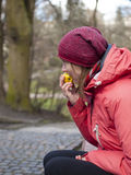 A young girl eats an Apple. Young and beautiful girl has a rest in the Park and eating a yellow Apple Royalty Free Stock Images