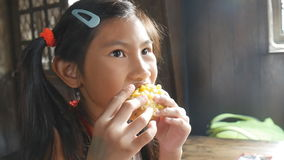 A young girl eats corn with day light stock video