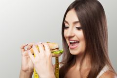 A young girl eats a hamburger and thinks of a diet. Slimming Res. Et excess weight. The concept of health and beauty. On a gray background Stock Photo