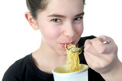 Young Girl eats noodles Royalty Free Stock Photography