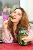 The young girl eats pickled cucumbers Stock Photography