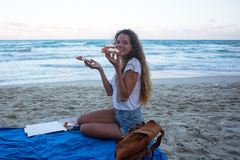 The young girl eats pizza on the beach, a dinner on the beach. Stock Images
