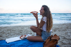 The young girl eats pizza on the beach, a dinner on the beach. Royalty Free Stock Photography