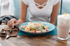Young girl eats at a restaurant. Caesar salad with chicken royalty free stock photos
