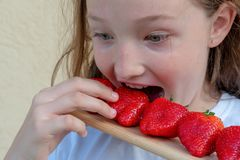 A young girl eats strawberries. Allergy in a child. Red face from strawberries royalty free stock photo