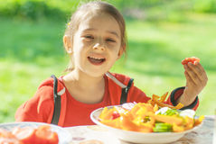 Young Girl eats vegetables Stock Photos