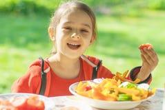 Young Girl eats vegetables Stock Photos