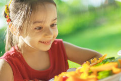 Young Girl eats vegetables Stock Images