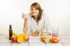 Young girl eats vegetarian vegetable salad with bread roll Stock Photo