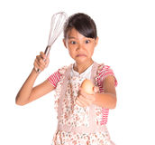Young Girl With Egg And Egg Beater II. Young Malay Asian girl in kitchen apron holding an egg beater with chicken egg over white background Stock Photos