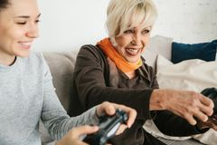 A young girl and an elderly woman play together in a video game. Joint pastime. Family life. Communication of the. A young girl and an elderly women play Stock Photo