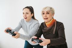 A young girl and an elderly woman play together in a video game. Joint pastime. Family life. Communication of the. A young girl and an elderly women play Stock Photography