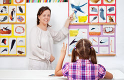 Young girl in elementary science class raising hand Royalty Free Stock Images