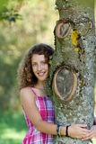 Young Girl Embracing Tree In Park Royalty Free Stock Photos