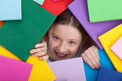 Young girl emerging from beneath books Royalty Free Stock Photography
