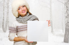 Young girl with empty card at snowy forest Royalty Free Stock Images