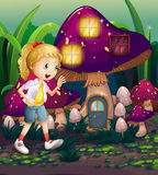 A young girl at the enchanted mushroom house Stock Photography