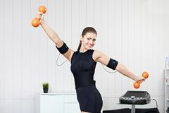 A young girl is engaged in fitness with dumbbells. On the electric muscle stimulation machine. EMS training stock photography