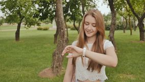 A young girl is engaged in a walk in the park, looking at a smart clock on her arm and receiving a pulse measurement. Health. Sport. Recreation. Summer stock footage