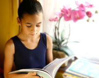 A young girl engross in her reading. Sitting by the window beautifully lit by the evening light Stock Photo