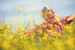 Young girl enjoy in blooming yellow field Stock Photography