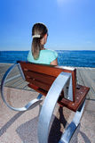 Young girl enjoying beautiful lakeview. Young female relaxing in a futuristic chair and enjoying a lake view at Lake Garda (Italy Stock Images