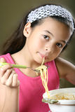 Young girl enjoying a bowl of pasta Stock Photo