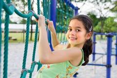 Young girl enjoying the climbing rope Stock Photo