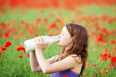 Young girl enjoying a drink of milk. From a glass bottle standing in field of red poppies Royalty Free Stock Photography