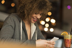 Young girl enjoying drink while playing on her phone. Young mixed race girl playing on her phone and smiling Royalty Free Stock Image