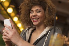 Young girl enjoying drink while playing on her phone Stock Photography