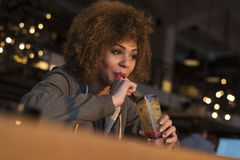 Young girl enjoying drink while playing on her phone Royalty Free Stock Photos