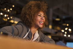 Young girl enjoying drink while playing on her phone. Young mixed race girl playing on her phone and smiling Stock Photography