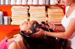 Young girl enjoying hair washing in beauty salon Stock Photos