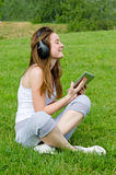 Young girl enjoying her music. Young girl with a blissful expression sitting crosslegged on the green grass wearing headphones enjoying her music from the tunes Stock Photography