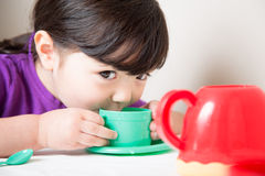 Young Girl Enjoying Her Tea. Young girl sipping from her cup having a tea party Royalty Free Stock Photography