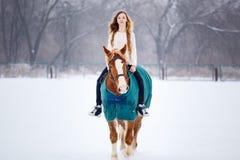 Young girl enjoying horseback riding in winter Stock Image