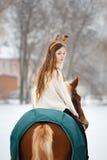 Young girl enjoying horseback riding in winter Royalty Free Stock Photo