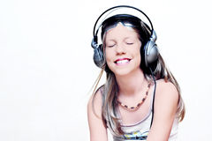 Young Girl Enjoying Music. Young girl with headphones, listening to music with closed eyes. Isolated on white background Royalty Free Stock Photos