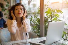 Young  girl enjoying music in headphones sitting with a laptop in a cafe. Stock Photos