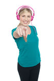 Young girl enjoying music and pointing at you Royalty Free Stock Photos