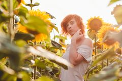 Young girl enjoying nature on the field of sunflowers at sunset, portrait of the beautiful redheaded woman girl with a sunflowers royalty free stock photos