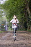 Young girl enjoying a ride on her space scooter Stock Images
