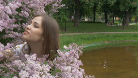 The young girl is enjoying the scent of lilac. Breathes the fragrance of flowers stock video