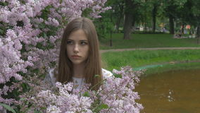 The young girl is enjoying the scent of lilac. Breathes the fragrance of flowers stock video footage